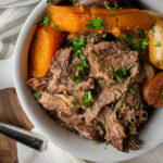 Whole30 beef roast with cooked carrots and potatoes. Garnished with chopped parsley.