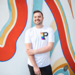 Brad smiling and standing in front of a colorful wall that is decorated with orange, light blue and yellow lines.