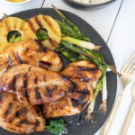 Grilled chicken breasts on a black plate served with grilled pineapple rings and green onions. A gold fork and knife sit alongside the plate and there are two bowls, one filled with white rice and one with additional grilled pineapple rings.